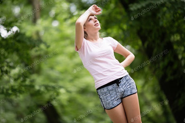 Exhausted female jogger grasping for air