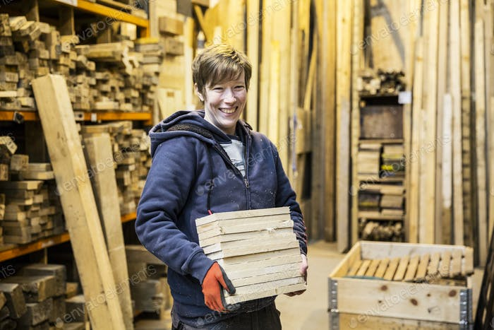 Smiling blond woman wearing work gloves standing in a workshop, holding stack of wood, looking at