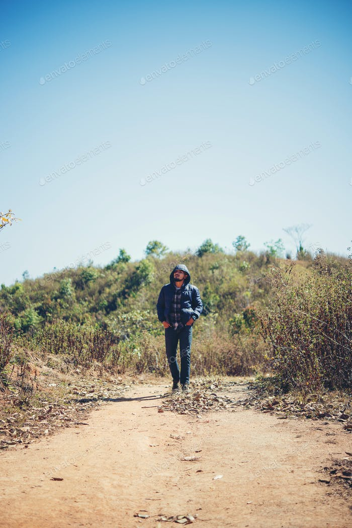 Hiker with backpack walking through forest enjoying adventure in holiday.
