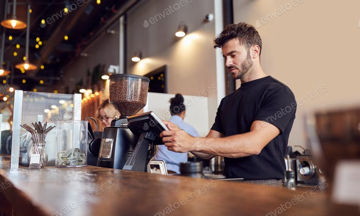 Male Coffee Shop Owner Working Behind Sales Desk