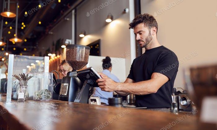 Male Coffee Shop Besitzer arbeiten hinter Sales Desk