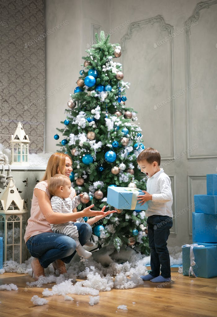 Young mother giving a present to the oldest son, baby boy touching bauble on Christmas tree