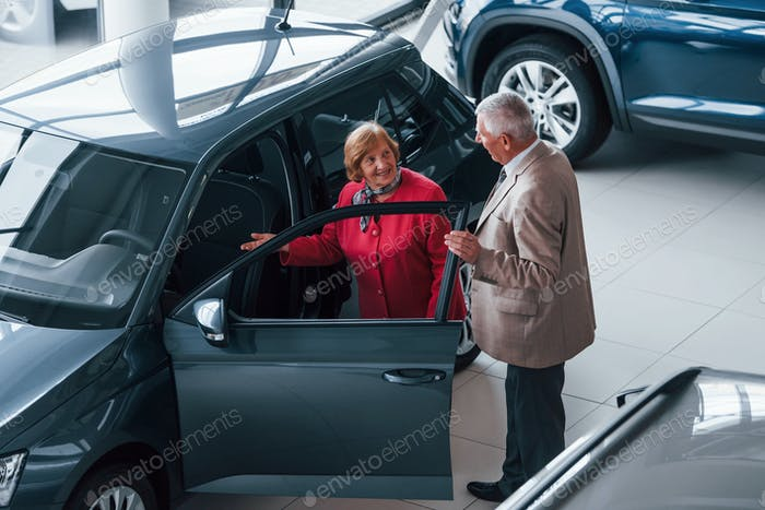 Aged man in formal wear supporting woman in choosing automobile