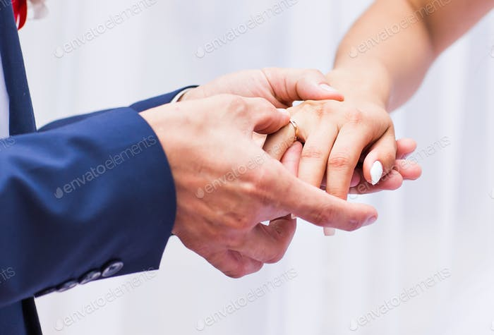 picture of man putting  wedding ring on woman hand