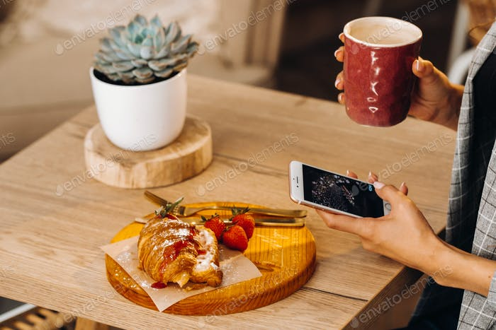 A girl is sitting at a table and texting on her smartphone in a cafe.A girl is sitting in a coffee