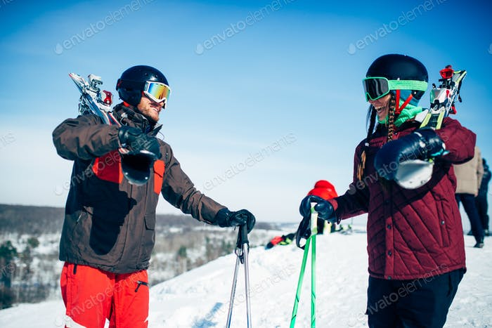 Male and female skiers poses with skis and poles