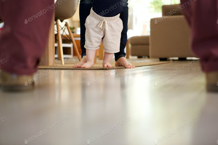 little baby boy learning to walk with mother help at home