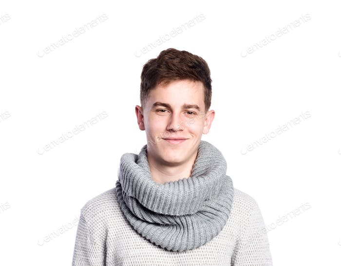 Teenage boy in gray sweater and scarf. Studio shot, isolated.