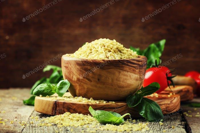 Raw barley bulgur in a wooden bowl