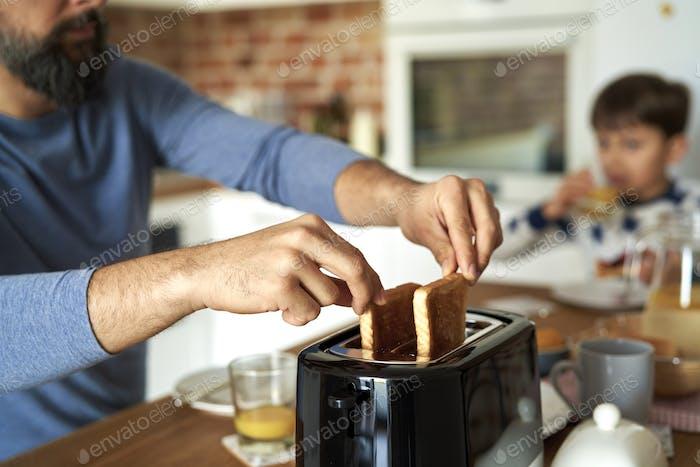 Nahaufnahme eines Mannes, der Toast aus einem Toaster zieht