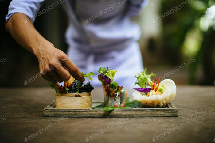 Close up of chef putting the final touches on a dish of salads and spring rolls.