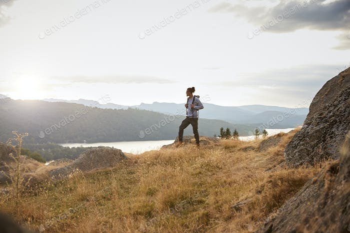 A young mixed race man standing alone on a rock admiring the lake view, side view