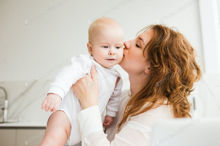 Beautiful mother standing and kissing her cute little baby