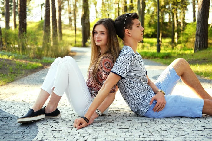 Lovely couple relaxing in summer park.