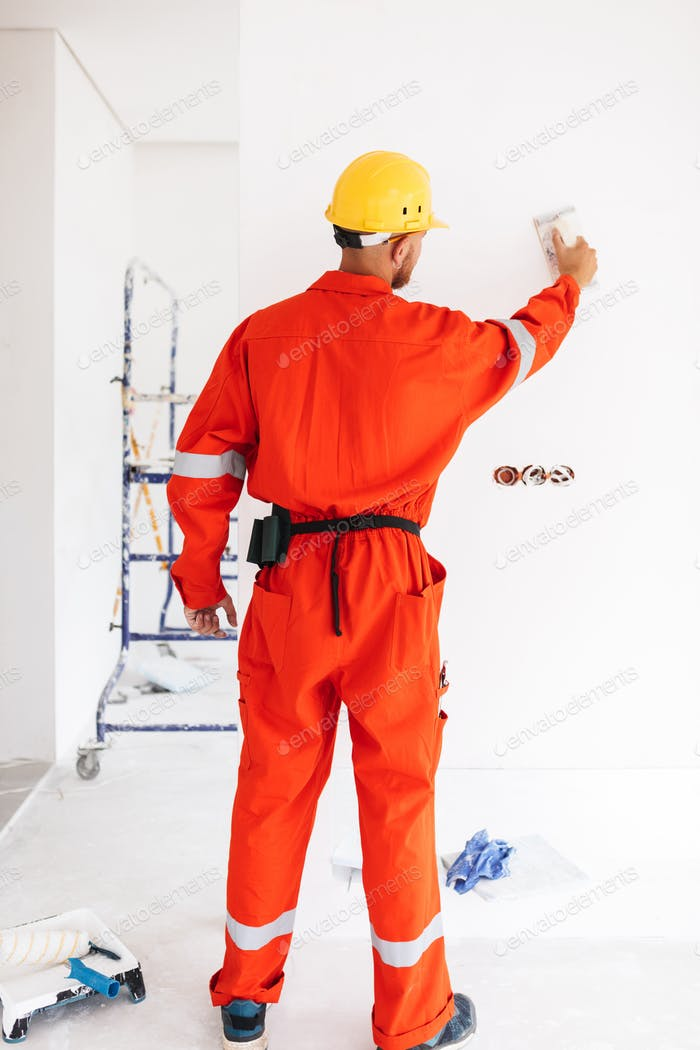 Young foreman standing from backside in orange work clothes and