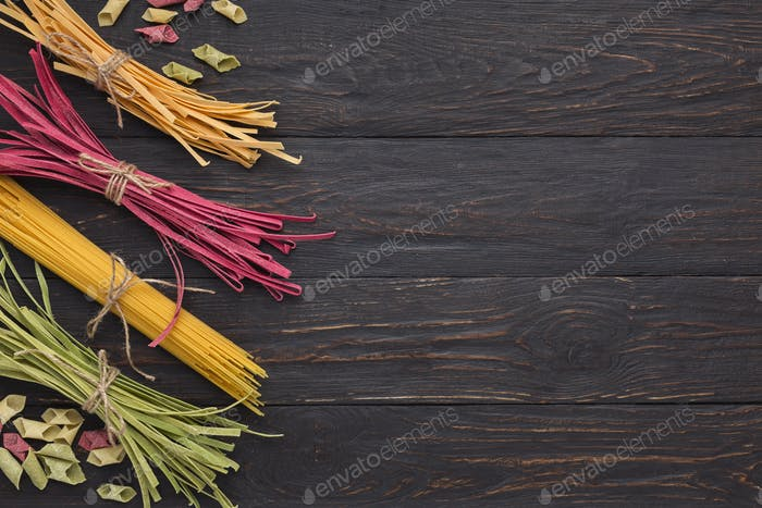 Pile of purple and green fettuccine pasta on wooden background