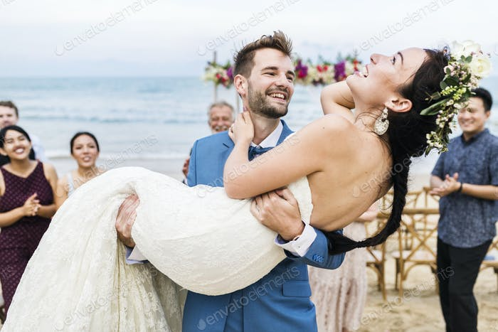 Cheerful newlyweds at beach wedding ceremony