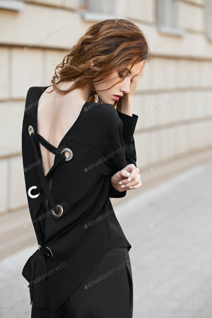 Brunette girl dressed in black blouse and trousers poses in the city street on a sunny day