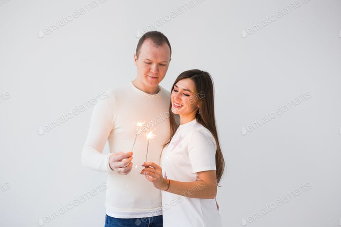 Romantic beautiful couple having date at Valentine's Day. Man and woman holding sparklers