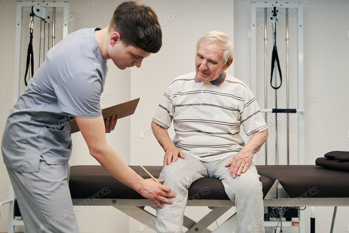 Manual therapist touching aching knee of elderly person