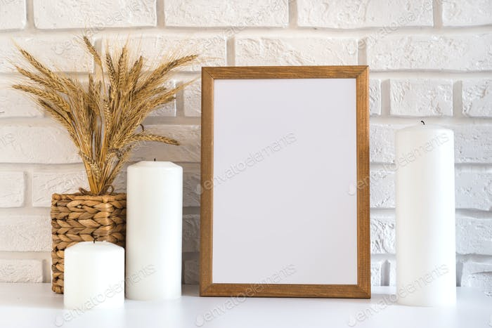 Blank wooden picture frame at the white brick wall