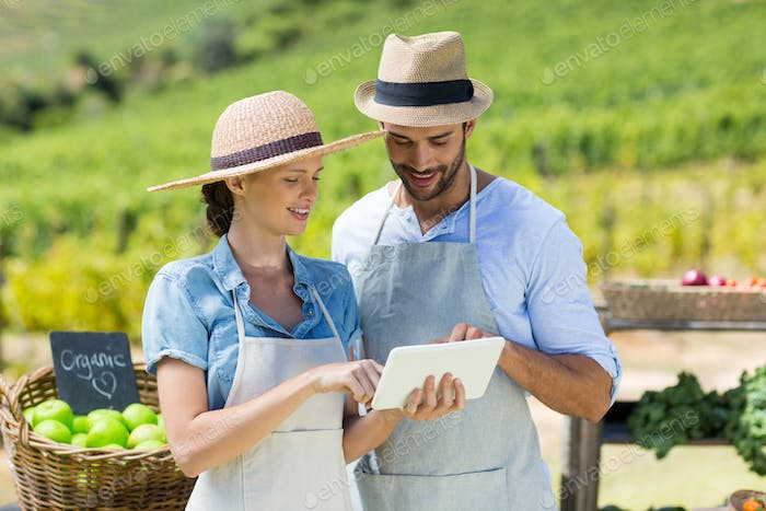 Happy couple using digital tablet at farm