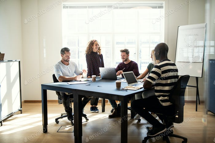 Smiling group of designers working together around an office table