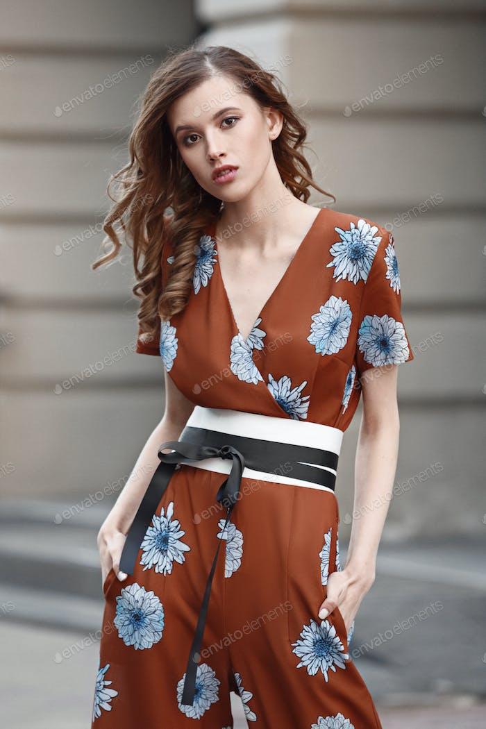 Schlank schönes Mädchen in einem stilvollen braun mit blauen Blumen Kleid gekleidet steht in einer Stadtstraße