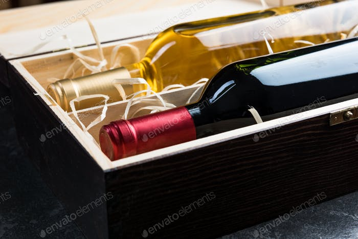 White and red wine bottles in wooden case