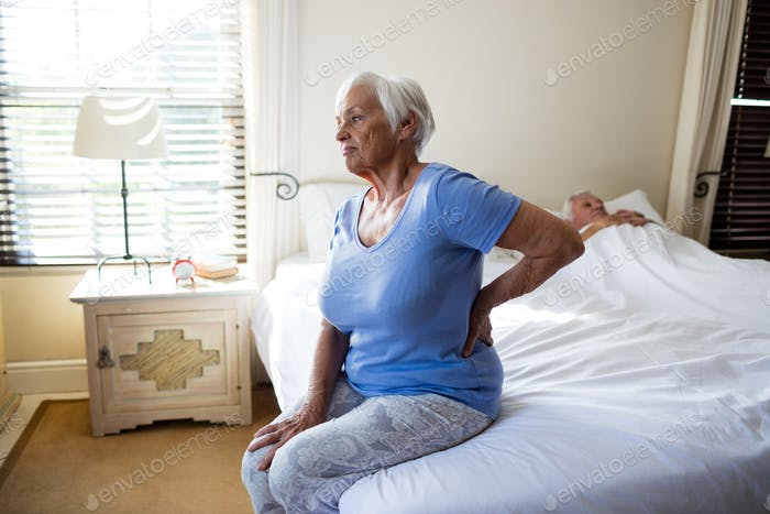 Senior woman suffering from backache in the bedroom
