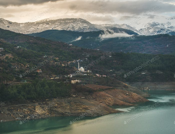 Dim Cay storage pond and mountains covered with snow, Alanya