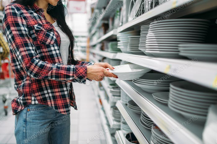 Young woman choosing plates in supermarket
