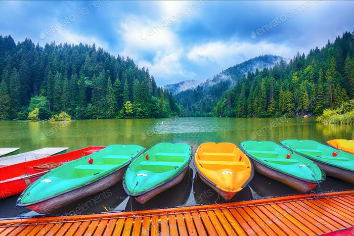 Boats on majestic mountain lake Lacul Rosu or Red Lake or Killer Lake