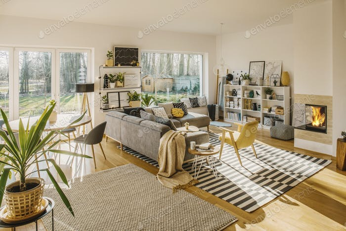 Two carpets on the floor in white Scandi living room interior wi