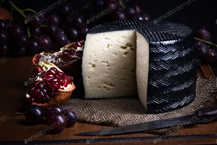 Spanish sheep cheese with grape and other fruit bodegon with classic light on wood