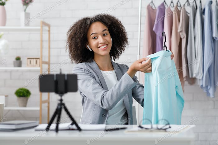 Happy african american lady recording online style lesson and showing blue shirt