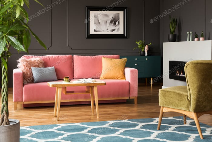 Green armchair and pink sofa in colorful living room interior wi