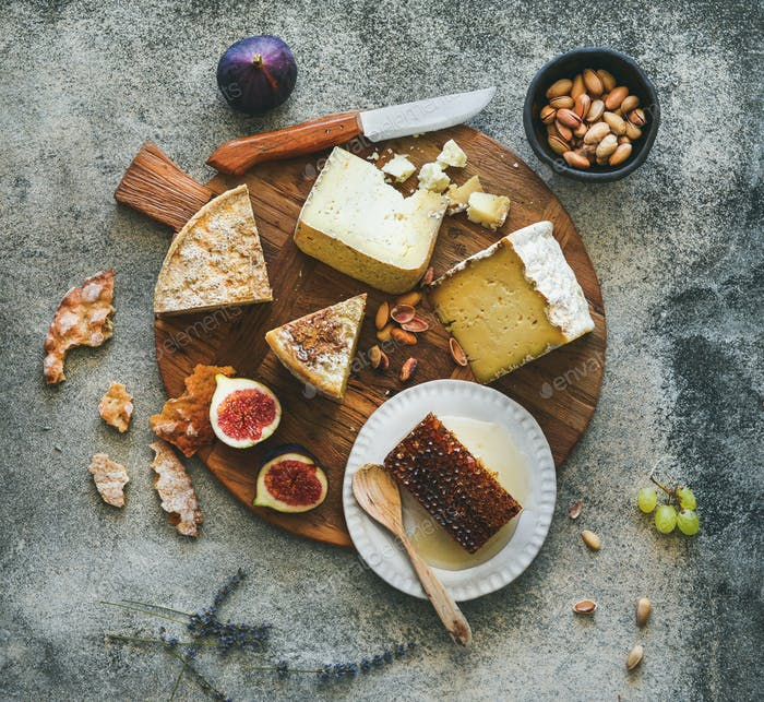 Flat-lay of cheese assortment, figs, honey and nuts
