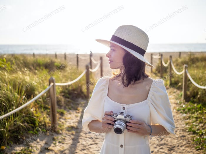 Young photographer in a white dress on the beach