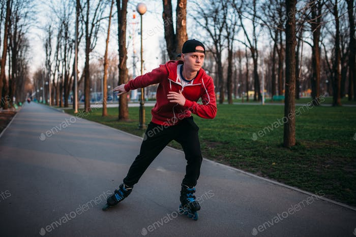 Roller skater rides by sidewalk in city park