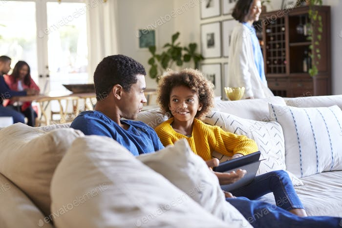 Father spending time with his pre-teen daughter on a sofa in the living room