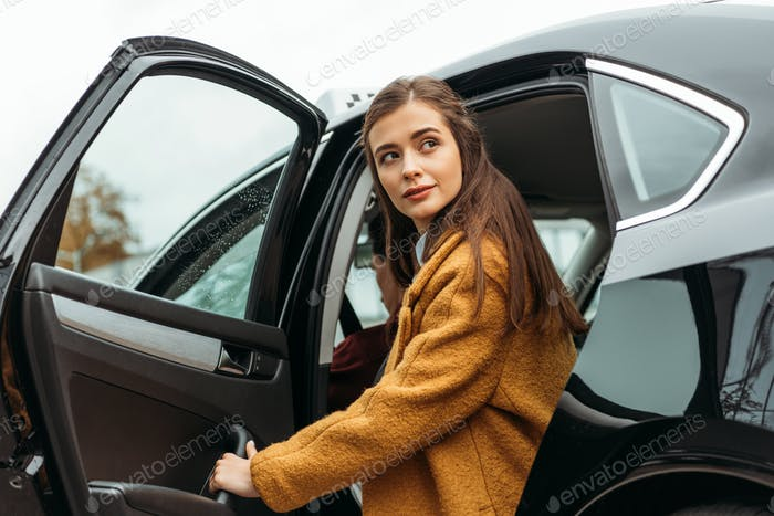 Young woman getting out of taxi and looking away