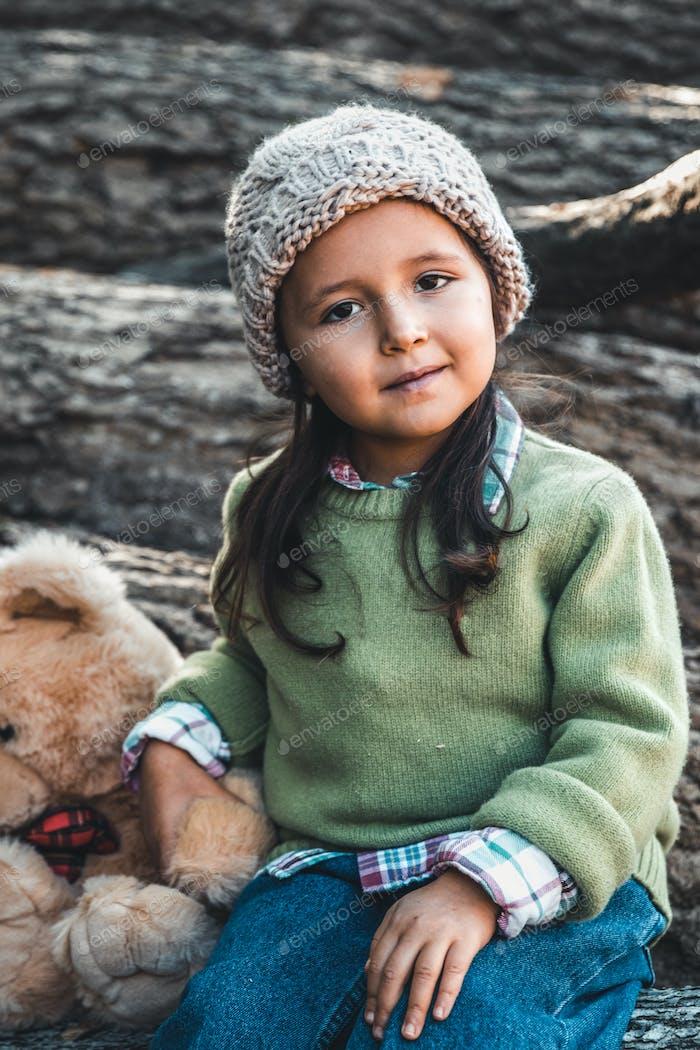 Kleines Mädchen mit einem Teddybär sitzt auf Baumstämmen