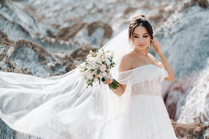 Beautiful bride in a wedding dress with a bouquet on the top of the salt mountains. A stunning young