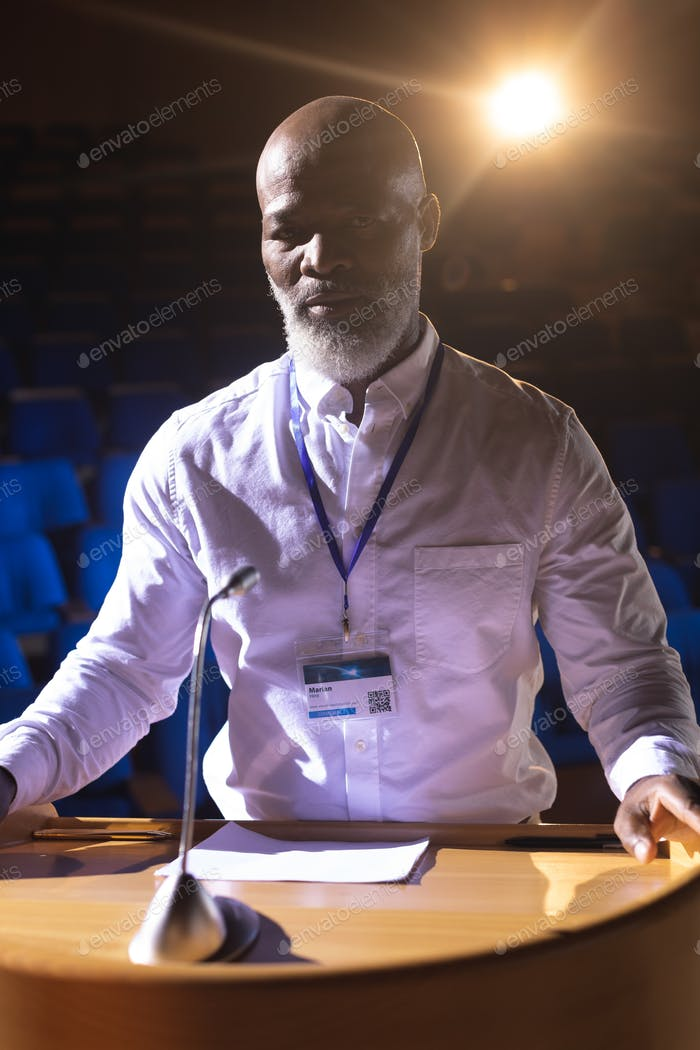Businessman standing at podium on stage in auditorium while looking at camera