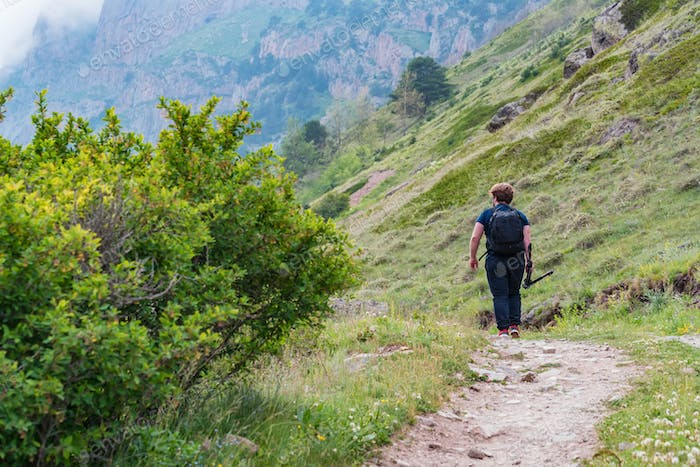 Back view male hiker walks in beautiful mountains in North Caucasus