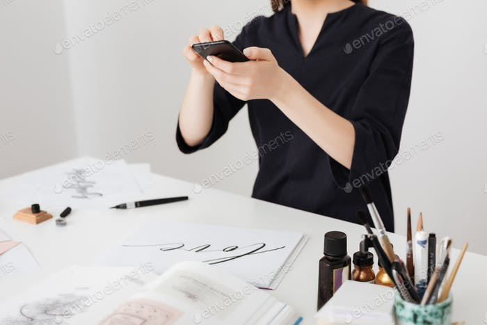 Girl sitting at the white desk and taking photos of notes on her cellphone isolated