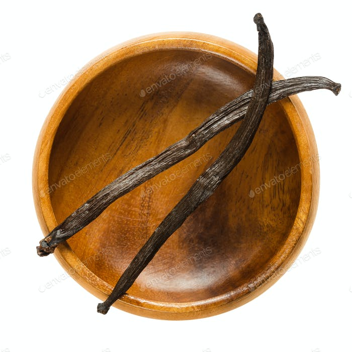 Dried Bourbon vanilla pods over empty wooden bowl