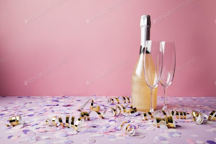 bottle of champagne, glasses and confetti pieces on violet tabletop