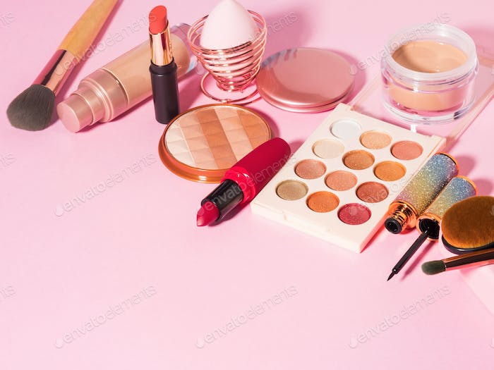 Different make up beauty cosmetics products on pink